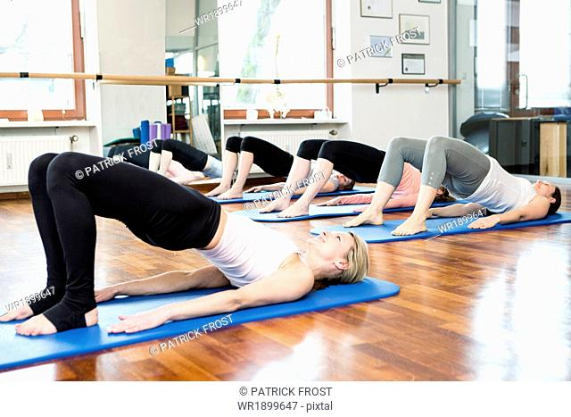 Group of women lying on back in Pilates class