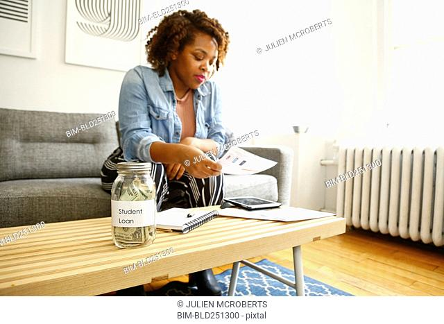 Mixed race woman with student loan reading paperwork