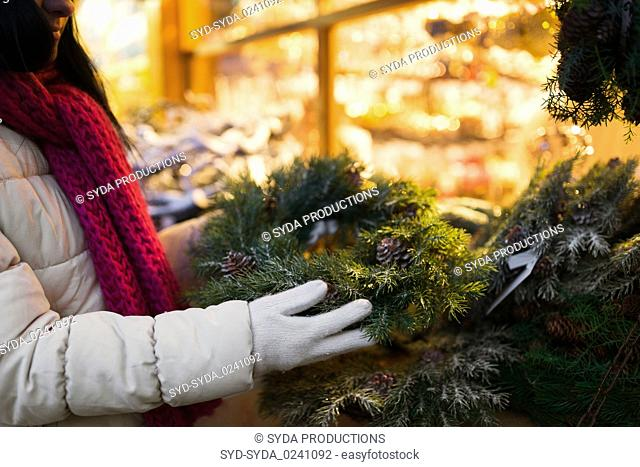 woman with fir tree wreath at christmas market