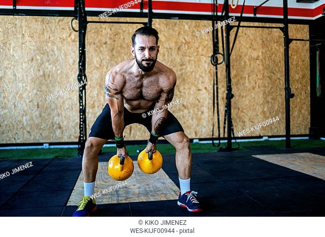Man lifting kettlebells in gym