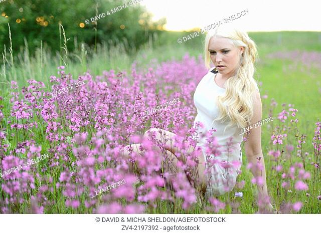 Close-up of a young woman in a flower field at sunset