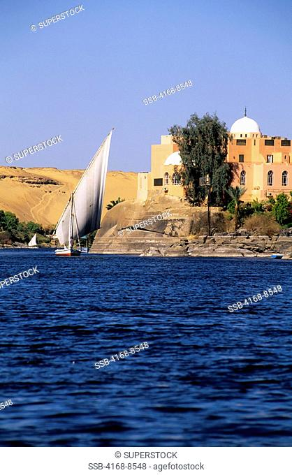 Egypt, Aswan, Nile River, Felucca with Club Med Tourist Resort in Background