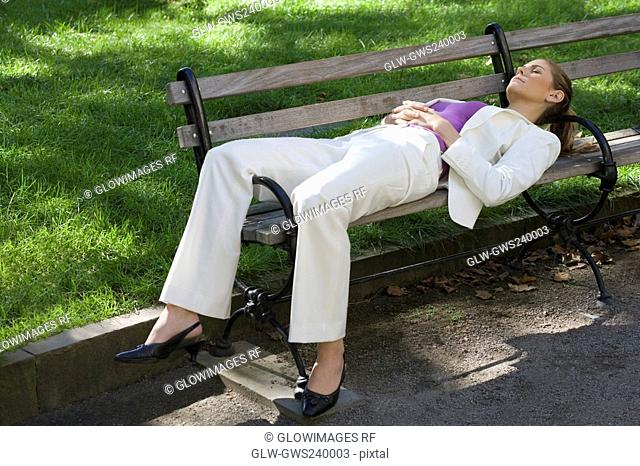 Businesswoman sleeping on a bench in a park