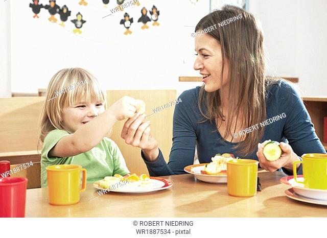 Girl and Female Carer Having Breakfast, Kottgeisering, Bavaria, Germany, Europe