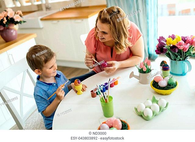 Family, mother and her son having fun paint and decorate eggs for holiday
