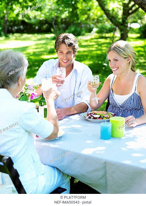 Three persons having dinner in the garden, Stockholm, Sweden