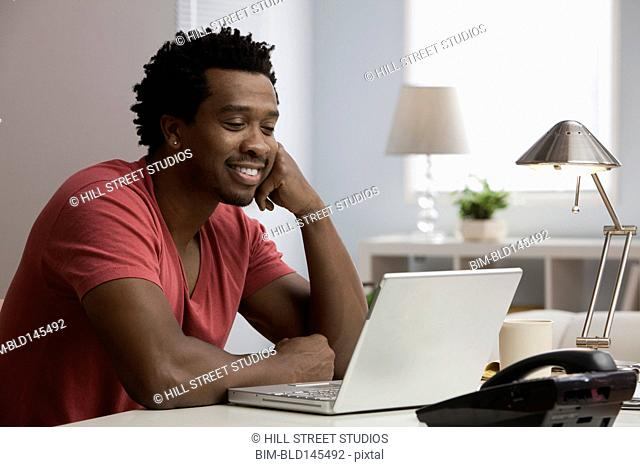 Smiling Black man working at desk in home office