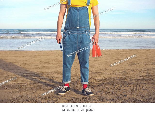 Man in dungarees standing on the beach holding bottles of soft drinks