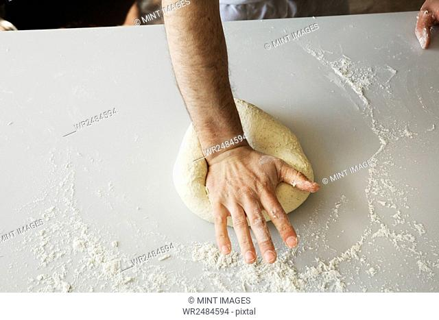 Close up of a baker kneading and shaping bread dough into a ball