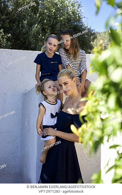 candid family portrait, mother with three daughters in garden. Australian ethnicity