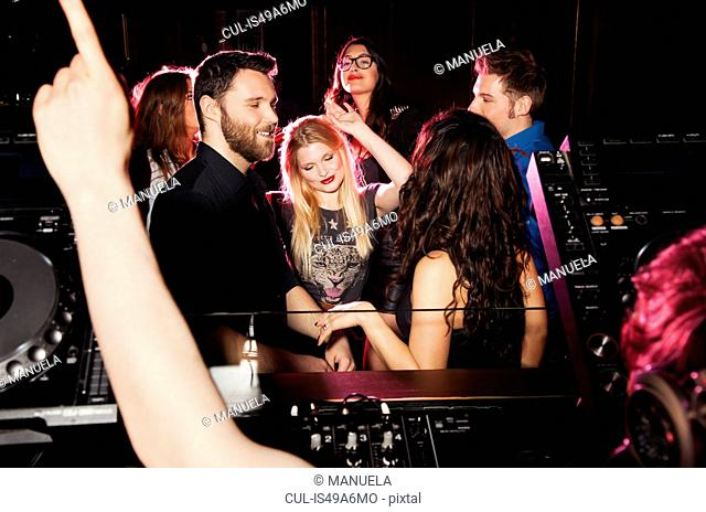 Group of young men and women dancing in front of DJ in nightclub