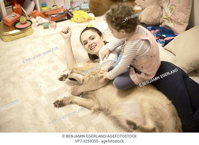 mother with toddler and dog lying on the floor in child's room, in Munich, Germany