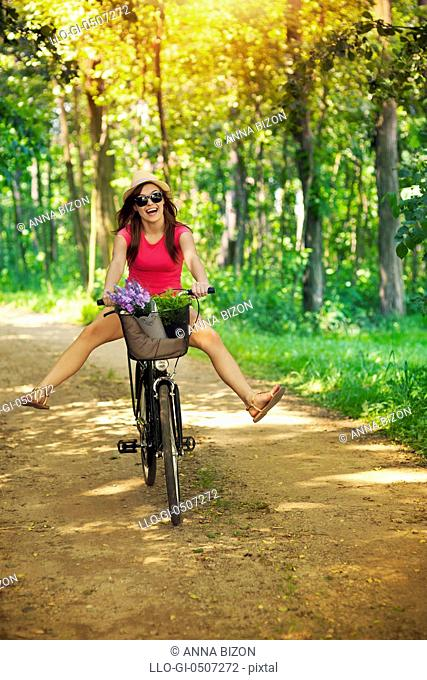 Happy woman enjoying a cycle ride in forest, Debica, Poland