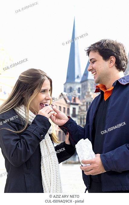 Romantic couple sharing confectionery, Ghent, Flanders, Belgium
