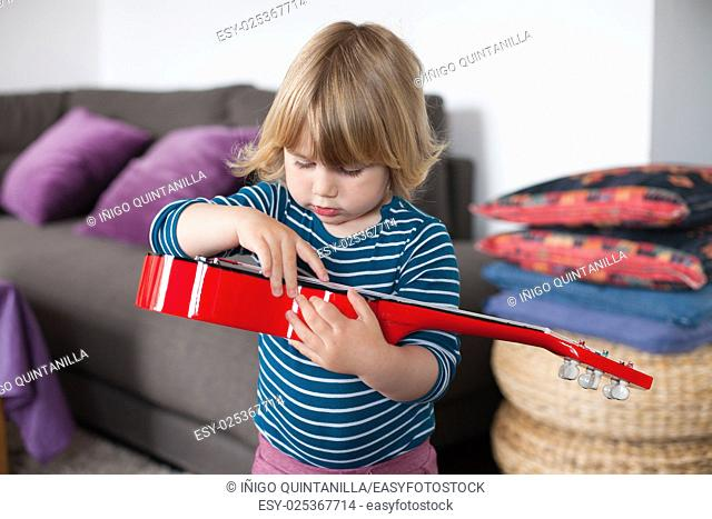 blonde two years old child with striped blue and white sweater inside home playing with hand red spanish little guitar