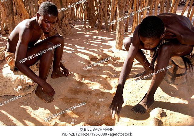 Namibia Africa remote Damara Tribe in Damaraland boys playing traditional game called llgus in native village