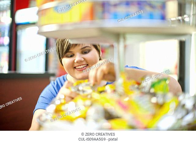 Young woman selecting confectionary in cafe