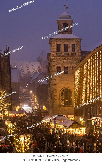 Visitors walk across the Christkindlesmarkt during snowfall in Nuremberg, Germany, 03 December 2017. Photo: Daniel Karmann/dpa