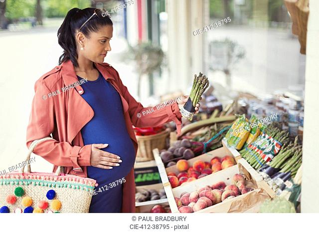Pregnant woman shopping for asparagus at market storefront