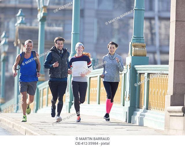 Runners running on sunny urban sidewalk