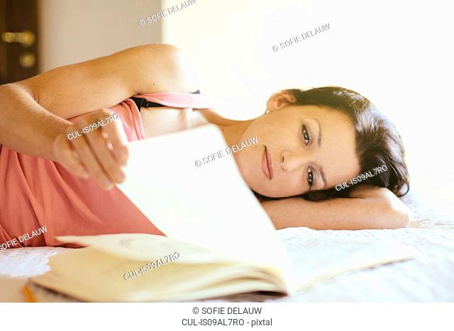 Mid adult woman lying on bed browsing notebook
