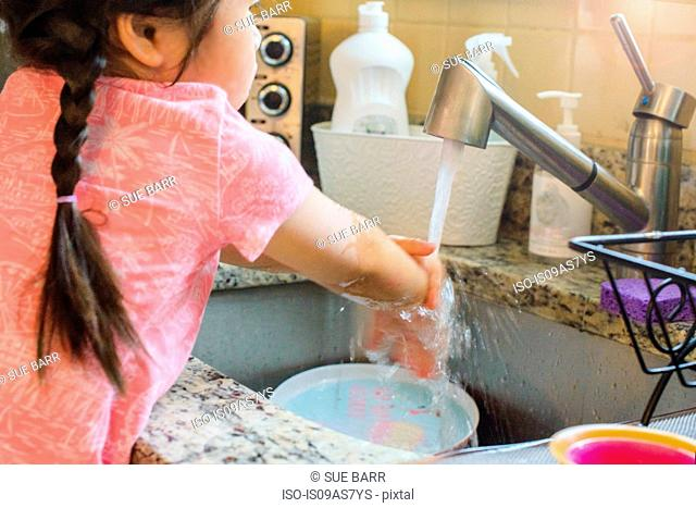 Young girl washing hands under tap