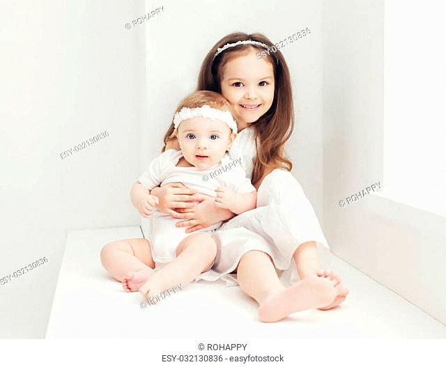 Two sisters little girls in white room at home near window