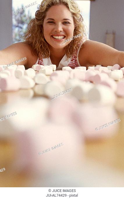 View of woman smiling with marshmallows in the foreground