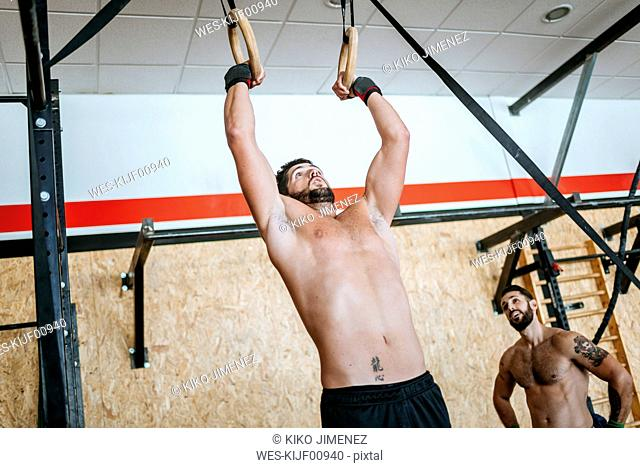 Man doing exercises on rings in gym
