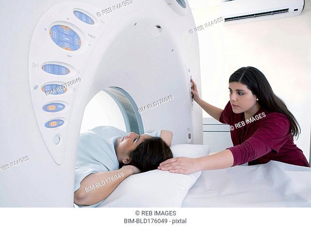 Hispanic nurse examining patient in MRI machine