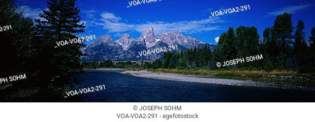 These are the mountain peaks along the Snake River in the Grand Tetons. There are trees along the river and a blue sky with white puffy clouds