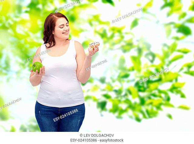 healthy eating, junk food, diet and choice people concept - smiling plus size woman choosing between apple and donut over green natural background
