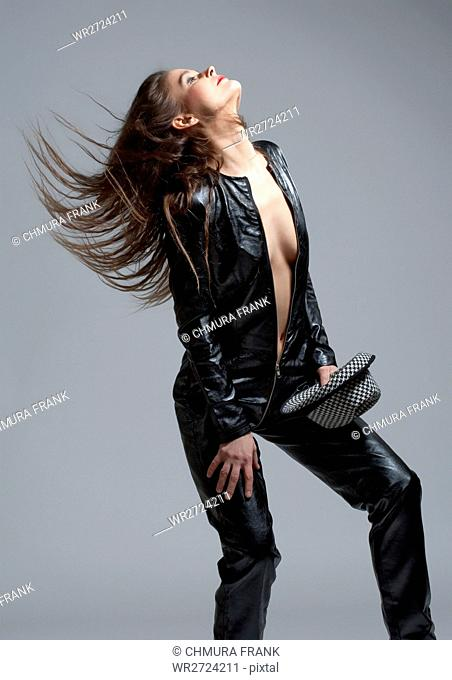 Woman in Leather Dress Holding a Hat and Hair Flying