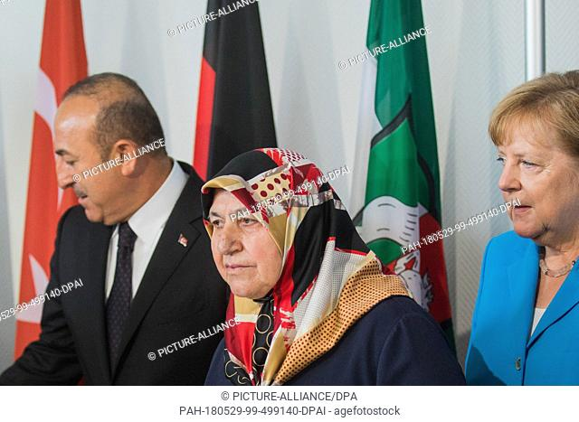 29 May 2018, Germany, Duesseldorf: Mevlude Genc (C), mother, grandmother, and aunt of victims, standing in the State Chancellery beside the German Chancellor...
