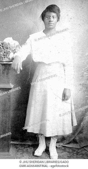 Full length portrait of young African American woman wearing glasses, a white blouse, and boots and standing with her arm resting on a table, 1944