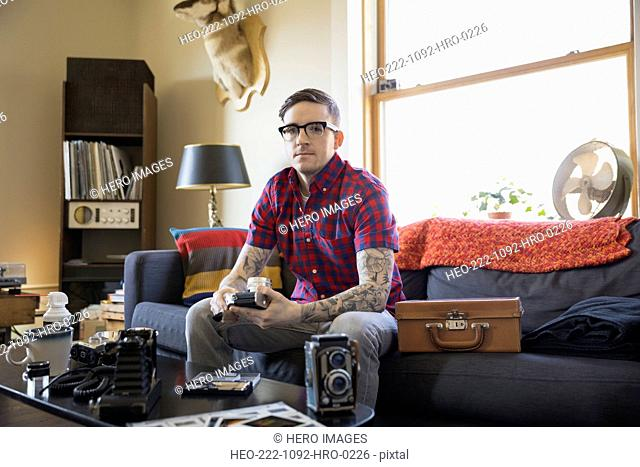 Portrait of serious man with antique cameras