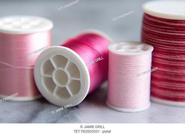 Variety of pink spools of thread