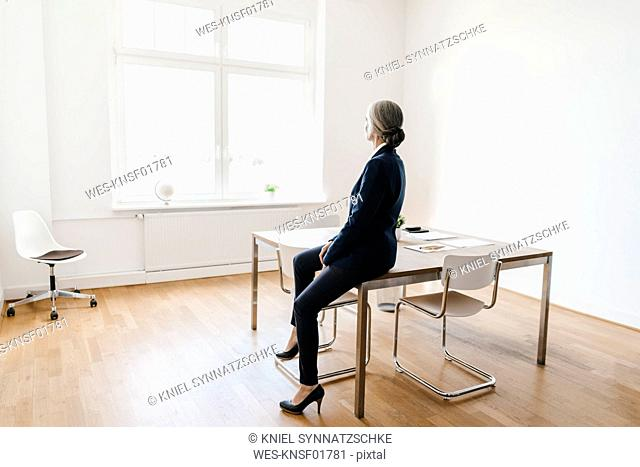 Businesswoman sitting on table in office looking out of window