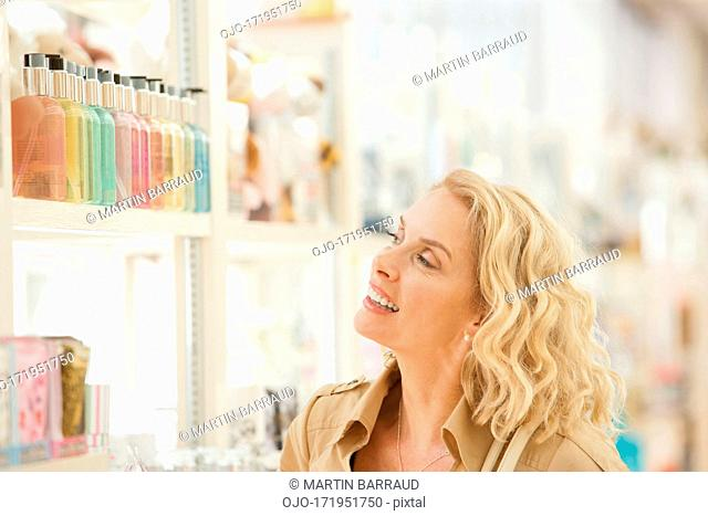 Smiling woman looking for perfume on store