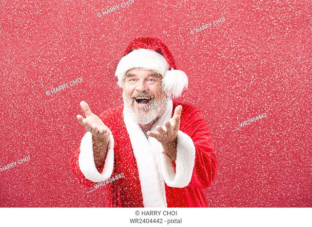 Portrait of smiling Santa holding hands in the snow