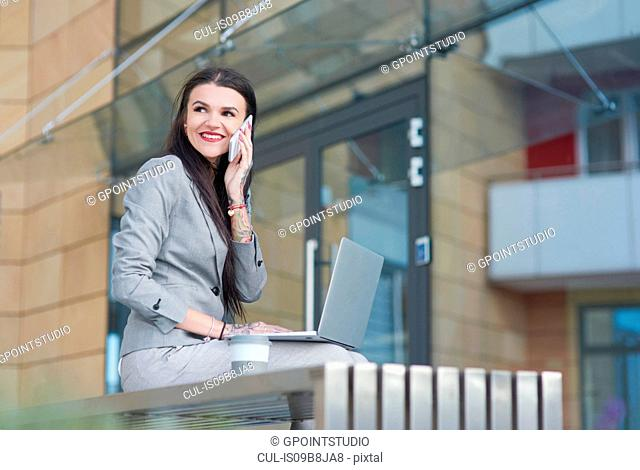 Businesswoman sitting outdoors, using laptop, holding smartphone to ear, smiling