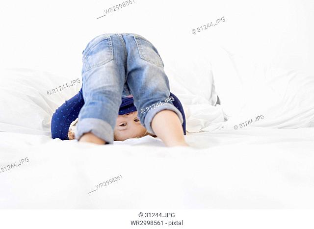 Girl with blond hair wearing jeans and blue top kneeling on a bed