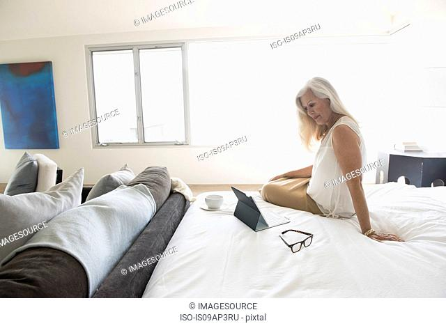 Senior woman sitting on bed and looking at tablet computer