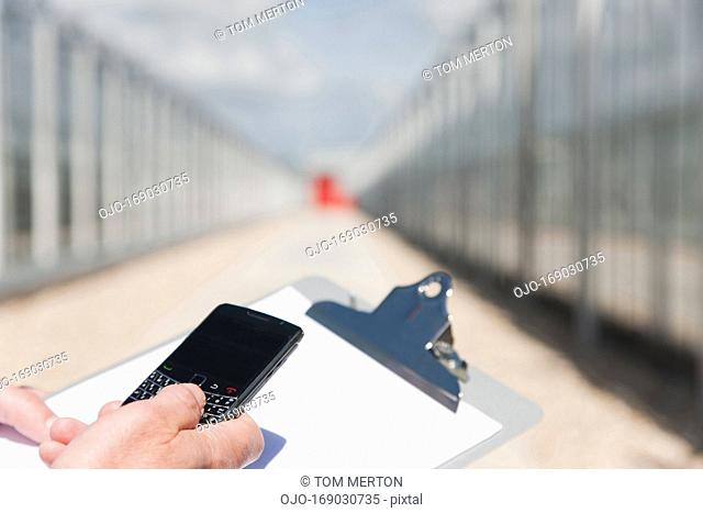 Scientist using cell phone outside greenhouses