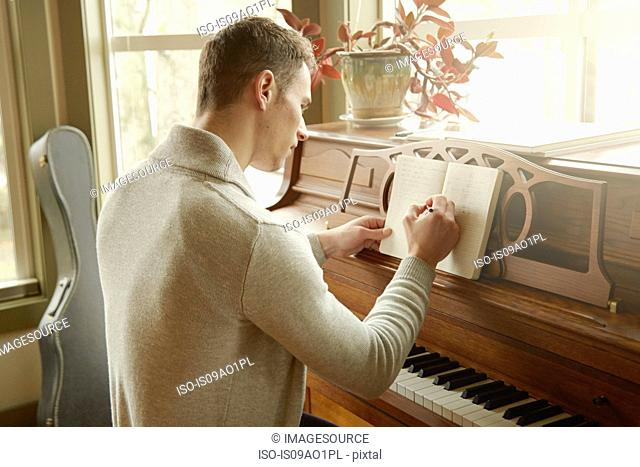 Young man writing in notebook whilst at the piano