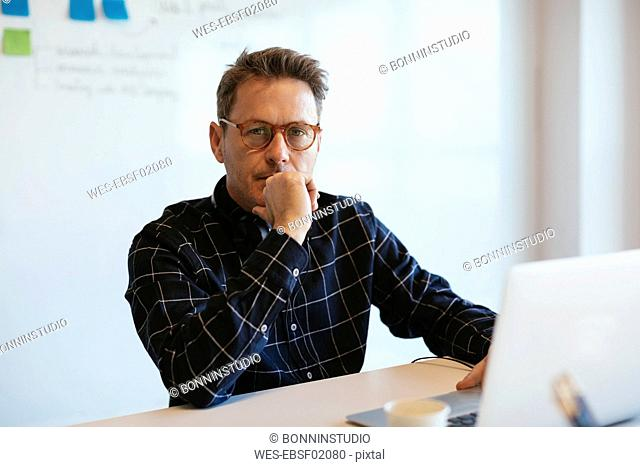 Portrait of serious businessman with laptop at desk in office