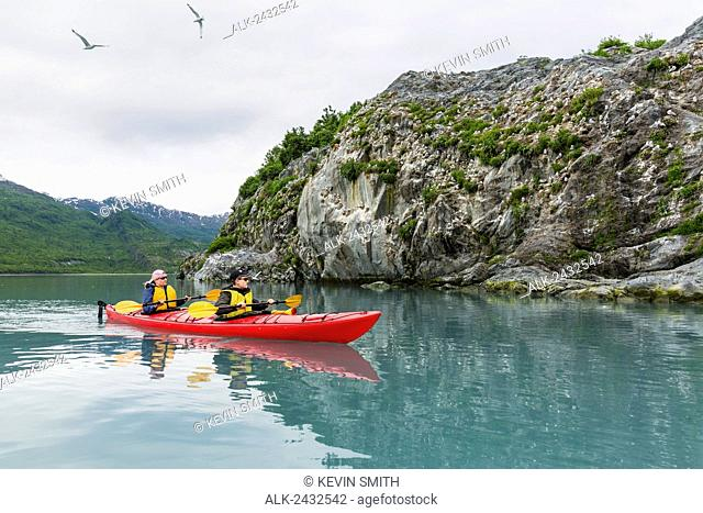 Mother and teen son sea kayaking in front of a Kittiwake bird rookery, Shoup Bay State Marine Park, Prince William Sound, Southcentral Alaska
