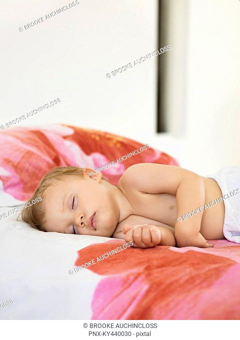 Baby boy sleeping in the bed