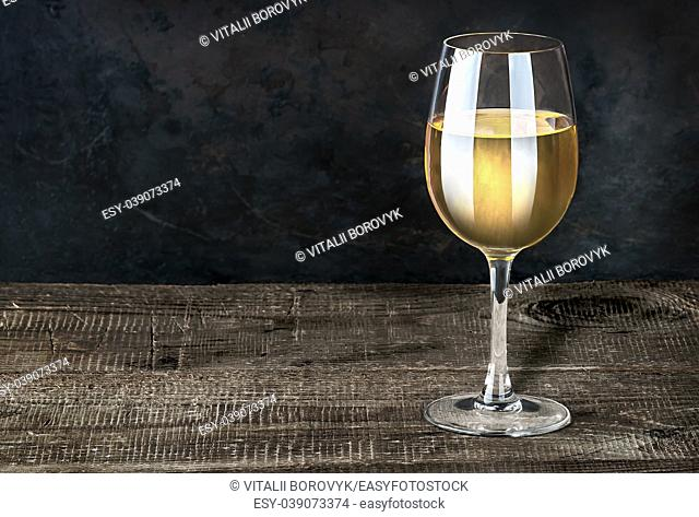 Glass of white wine on a wooden table. Dark background. Wooden table of plates