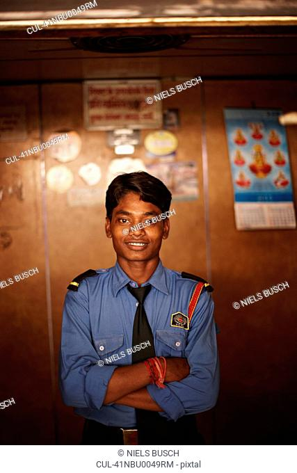 Smiling police officer with arms folded